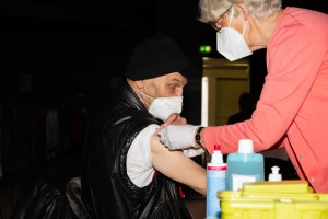 Eine Ärztin setzt am Arm eines Wohnungslosen eine Spritze an, um ihn zu impfen.