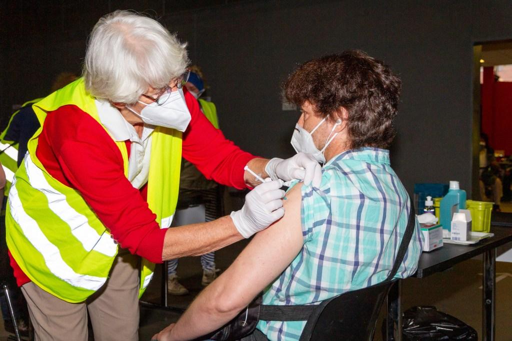 Eine Ärztin setzt am Arm eines Wohnungslosen eine Spritze an, um ihn zu impfen